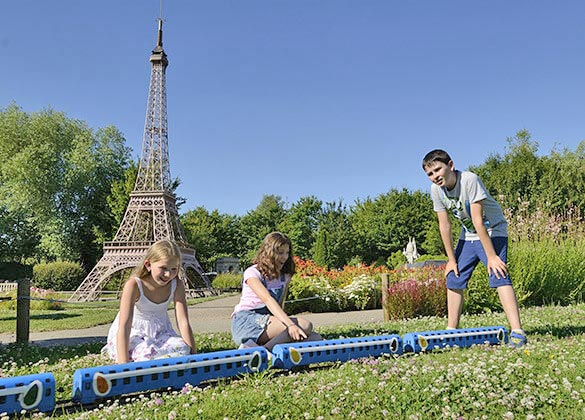 enfants devant un petit train et la Tour Eiffel au parc France Miniature